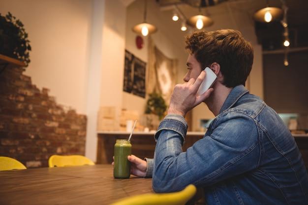 Equipaggi la conversazione sul telefono cellulare mentre mangiano il succo