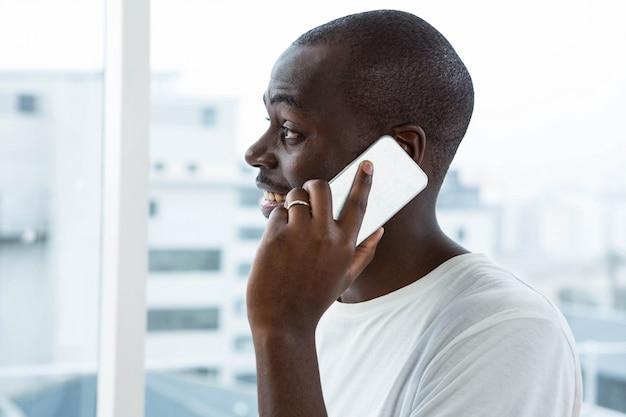 Equipaggi la conversazione sul telefono cellulare vicino alla finestra a casa