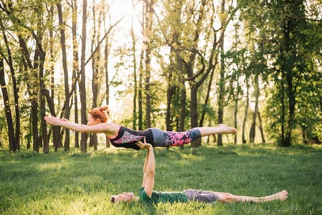 Equipaggi la donna d'equilibratura sulla sua mano mentre fanno l'yoga nel campo erboso