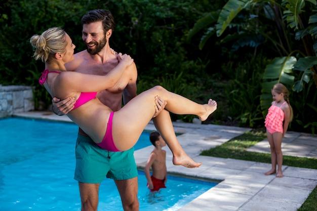 Equipaggi la donna di trasporto a bordo piscina con i bambini nel fondo
