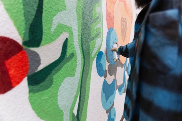 Equipaggi la fabbricazione dei graffiti con la latta dell'aerosol sulla parete