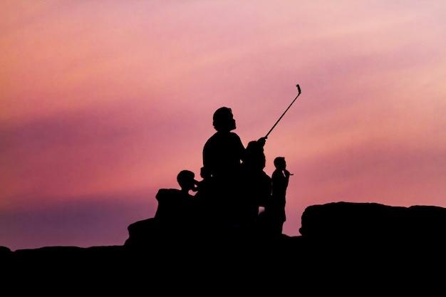 Equipaggi la fotografia della siluetta e selfie con la montagna al tramonto.