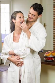 Equipaggi la fragola d'alimentazione alla donna in cucina