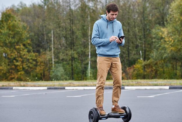 Equipaggi la guida sul bordo di hover e per mezzo dello smartphone all'aperto