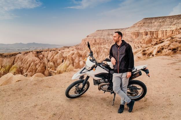 Equipaggi la guida sulla motocicletta nel paesaggio della montagna di cappadocia al tramonto