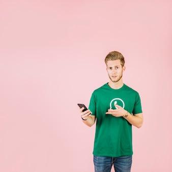 Equipaggi la maglietta dell'icona di whatsapp che gesturing mentre tengono il telefono cellulare