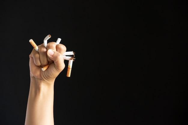 Equipaggi la mano che schiaccia e che distrugge le sigarette su fondo nero.
