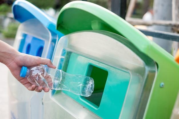 Equipaggi la mano che tiene e che mette lo spreco di plastica della bottiglia nei rifiuti dell'immondizia.