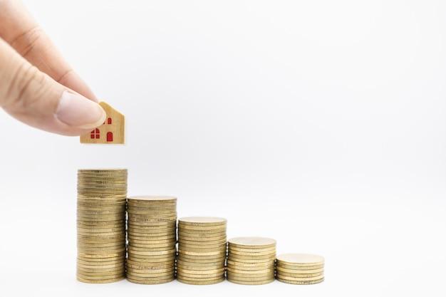 Equipaggi la mano che tiene il giocattolo di legno della casa e che posa sopra la pila di monete di oro su bianco.