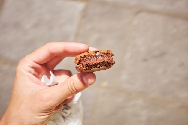 Equipaggi la mano che tiene il macaron francese del chocolatte su fondo grigio