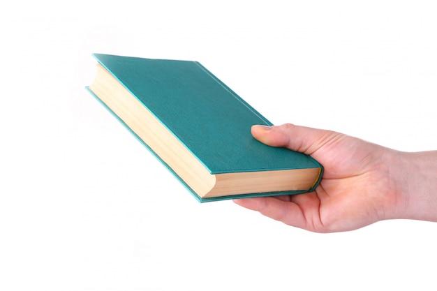 Equipaggi la mano che tiene il vecchio libro verde su fondo bianco