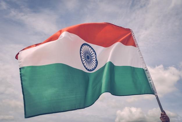 Equipaggi la mano che tiene la bandiera dell'india sul cielo blu