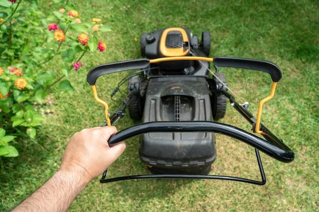 Equipaggi la mano che tiene una macchina della falciatrice da giardino al taglio dell'erba verde