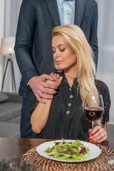 Equipaggi la mano della tenuta della donna bionda alla tavola