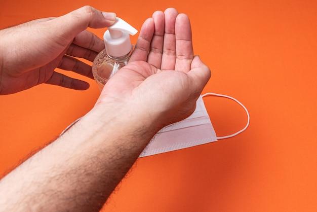 Equipaggi la mano in contenitore con il gel dell'alcool sulla parete arancio