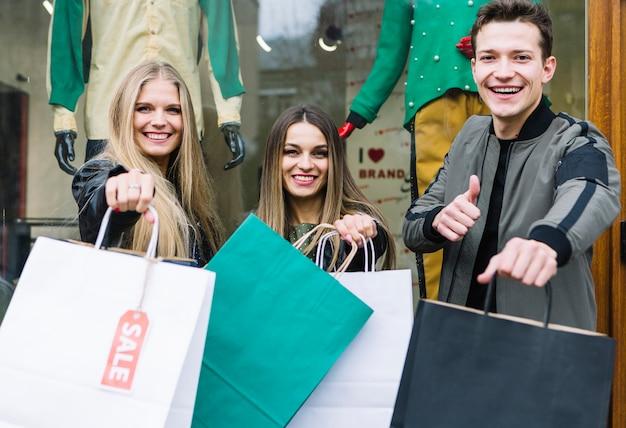 Equipaggi la mostra del pollice sul segno con i suoi amici che tengono i sacchetti della spesa