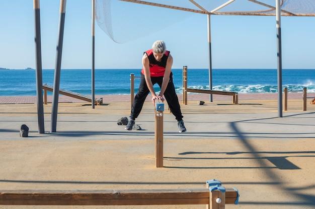 Equipaggi la pratica dello sport in una palestra urbana di legno all'aperto, vicino al mare.