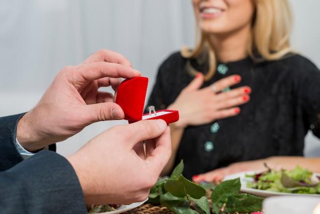 Equipaggi la presentazione del contenitore di regalo con l'anello alla donna sorpresa alla tavola
