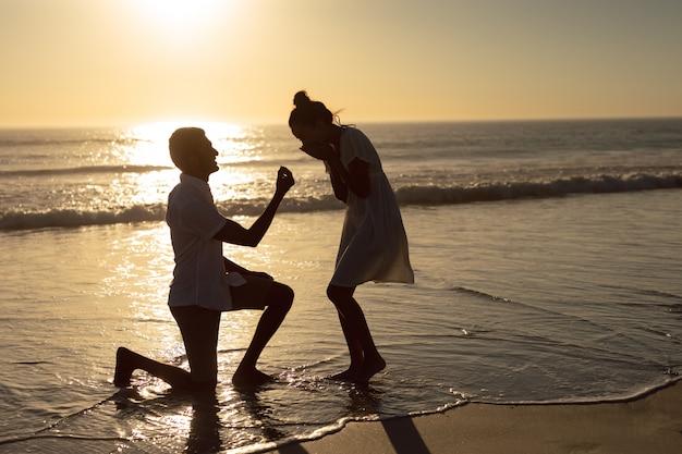 Equipaggi la proposta della donna alla spiaggia sulla spiaggia