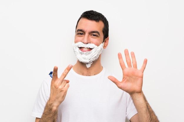 Equipaggi la rasatura della sua barba sopra fondo bianco isolato che conta sette con le dita