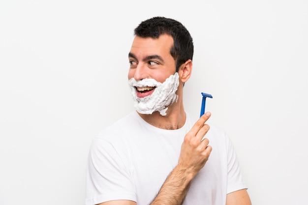 Equipaggi la rasatura della sua barba sopra fondo bianco isolato con le armi attraversate e felici