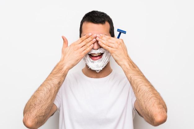 Equipaggi la rasatura della sua barba sopra gli occhi bianchi isolati della copertura murale a mano