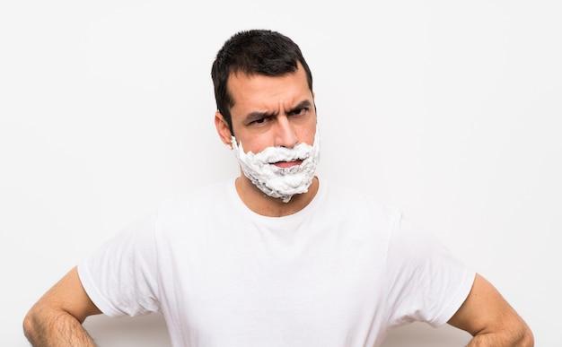 Equipaggi la rasatura della sua barba sopra la parete bianca isolata arrabbiata