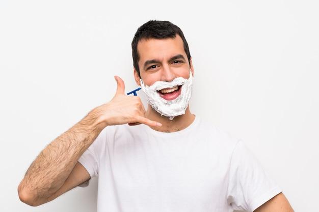 Equipaggi la rasatura della sua barba sopra la parete bianca isolata che fa il gesto del telefono. richiamami segno