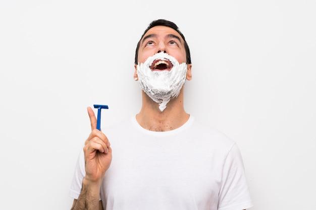 Equipaggi la rasatura della sua barba sopra la parete bianca isolata che indica su e sorpreso