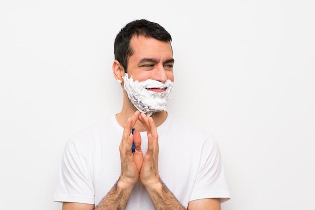 Equipaggi la rasatura della sua barba sopra la parete bianca isolata che progetta qualcosa