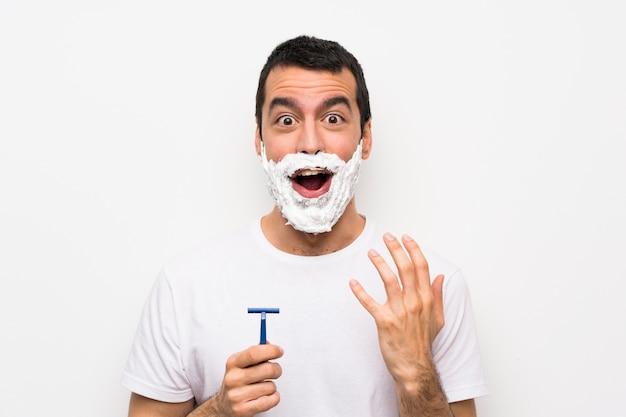 Equipaggi la rasatura della sua barba sopra la parete bianca isolata con espressione facciale di sorpresa