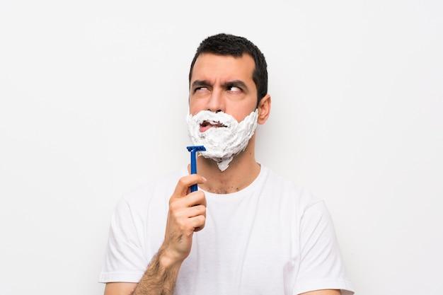 Equipaggi la rasatura della sua barba sopra la parete bianca isolata con l'espressione confusa del fronte