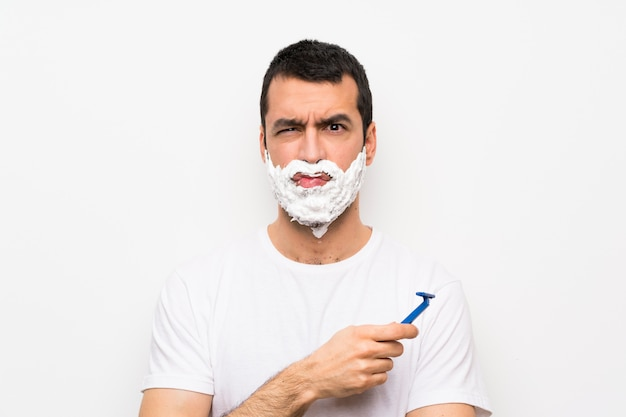 Equipaggi la rasatura della sua barba sopra la parete bianca isolata con l'espressione triste e depressa