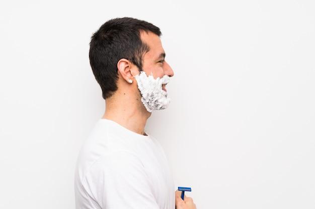 Equipaggi la rasatura della sua barba sopra la parete bianca isolata nella posizione laterale