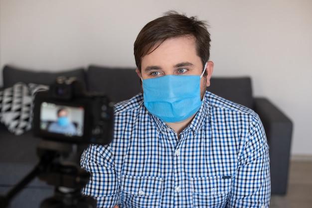Equipaggi la registrazione del video, usando la macchina fotografica digitale in ufficio oa casa, il coronavirus, la malattia, l'infezione, la quarantena, la mascherina medica
