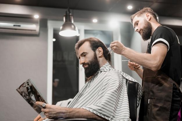 Equipaggi la rivista della lettura mentre tagliano i capelli nel negozio di barbiere