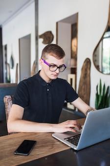 Equipaggi la seduta con il computer portatile in caffè