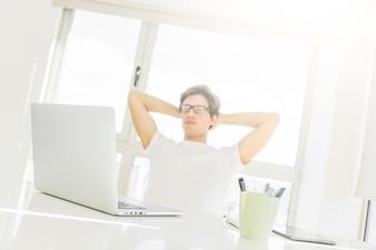 Equipaggi la seduta davanti al computer portatile con le mani dietro la testa
