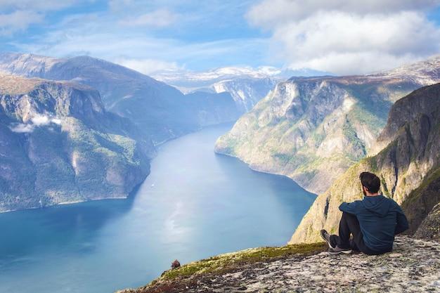 Equipaggi la seduta sul bordo della scogliera da solo godendo le vacanze estive zaino in spalla di viaggio di stile di vita di avventura aerea di viaggio di vista aerea nella cima della norvegia di bello cielo blu della montagna
