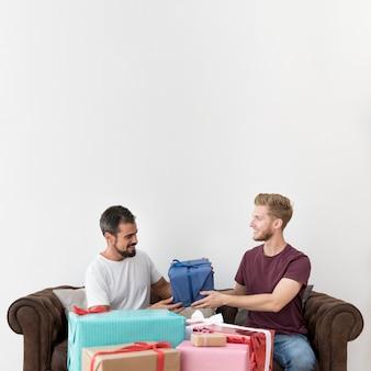 Equipaggi la seduta sul sofà che prende il contenitore di regalo contro fondo bianco