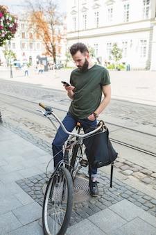 Equipaggi la seduta sulla bicicletta facendo uso del telefono cellulare
