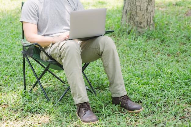 Equipaggi la seduta sulla sedia di campeggio e lavorare con il computer portatile nel giardino