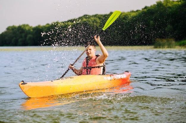 Equipaggi la spruzzatura dell'acqua con la pagaia mentre kayaking sul lago