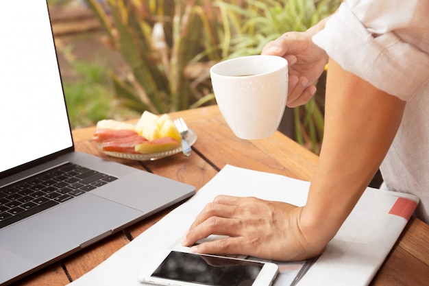Equipaggi la tazza da caffè della tenuta della mano con il computer portatile ed il giornale, telefono cellulare sul tavolo.