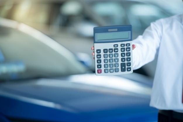 Equipaggi la tenuta del calcolatore nello showroom dell'automobile, uomo che preme il calcolatore per finanza di affari sullo showroom dell'automobile