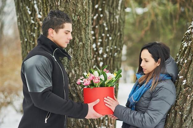 Equipaggi la tenuta del contenitore di regalo rosso con il bello mazzo dei tulipani rosa, gialli e bianchi di fioritura e dei crisantemi bianchi con le foglie verdi, all'aperto