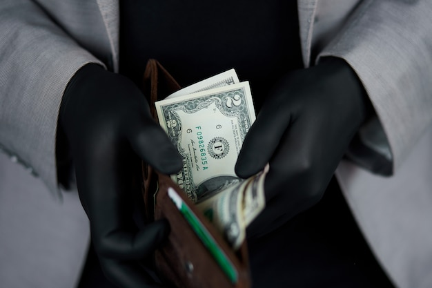 Equipaggi la tenuta del portafoglio con i dollari dei soldi in mano con i guanti medici neri.