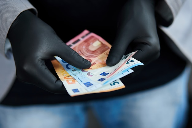 Equipaggi la tenuta del portafoglio con l'euro dei soldi a disposizione in guanti medici neri