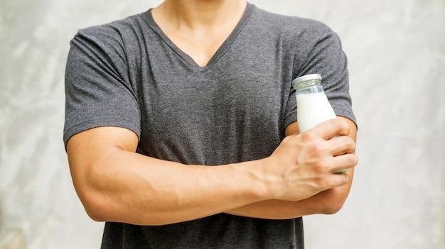 Equipaggi la tenuta della bottiglia di latte su fondo grigio.