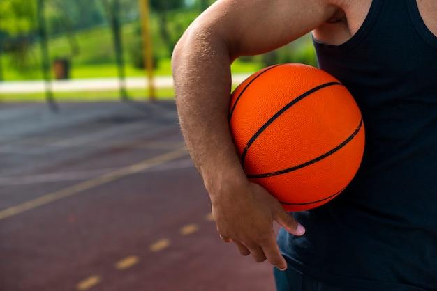 Equipaggi la tenuta della palla sul primo piano del campo da pallacanestro